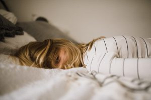 young woman falling asleep on bed fully dressed